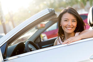 Beautiful female driver in a convertible car smiling