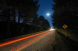 Cars pass on a country road at night with the moon above