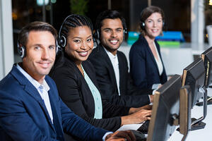 Portrait of group of business colleagues with headsets using computer at office desk